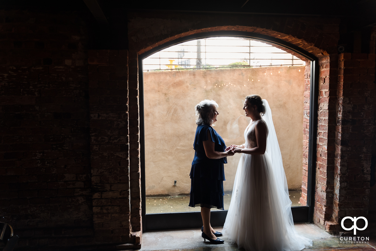 Bride and her mother standing in the window at The Old Cigar Warehouse.