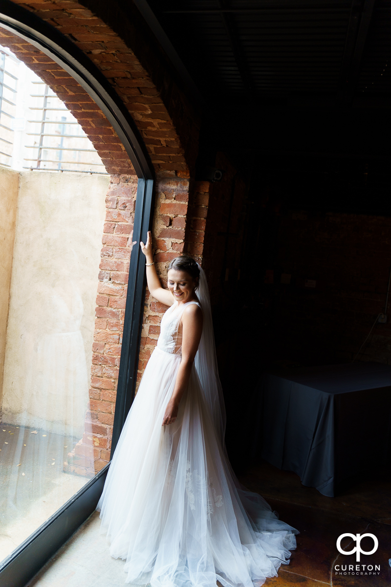 Bride standing in the window of The Old Cigar Warehouse.