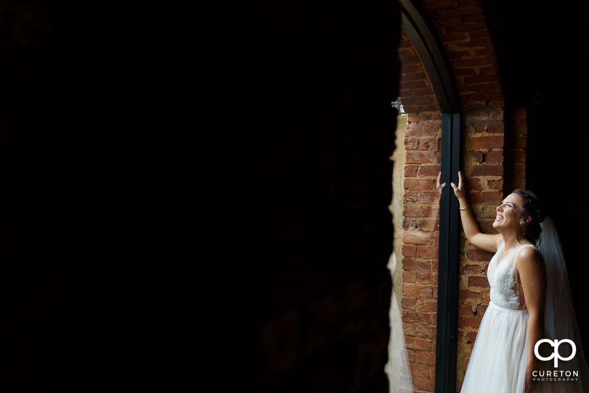 Bride laughing while looking out the window.
