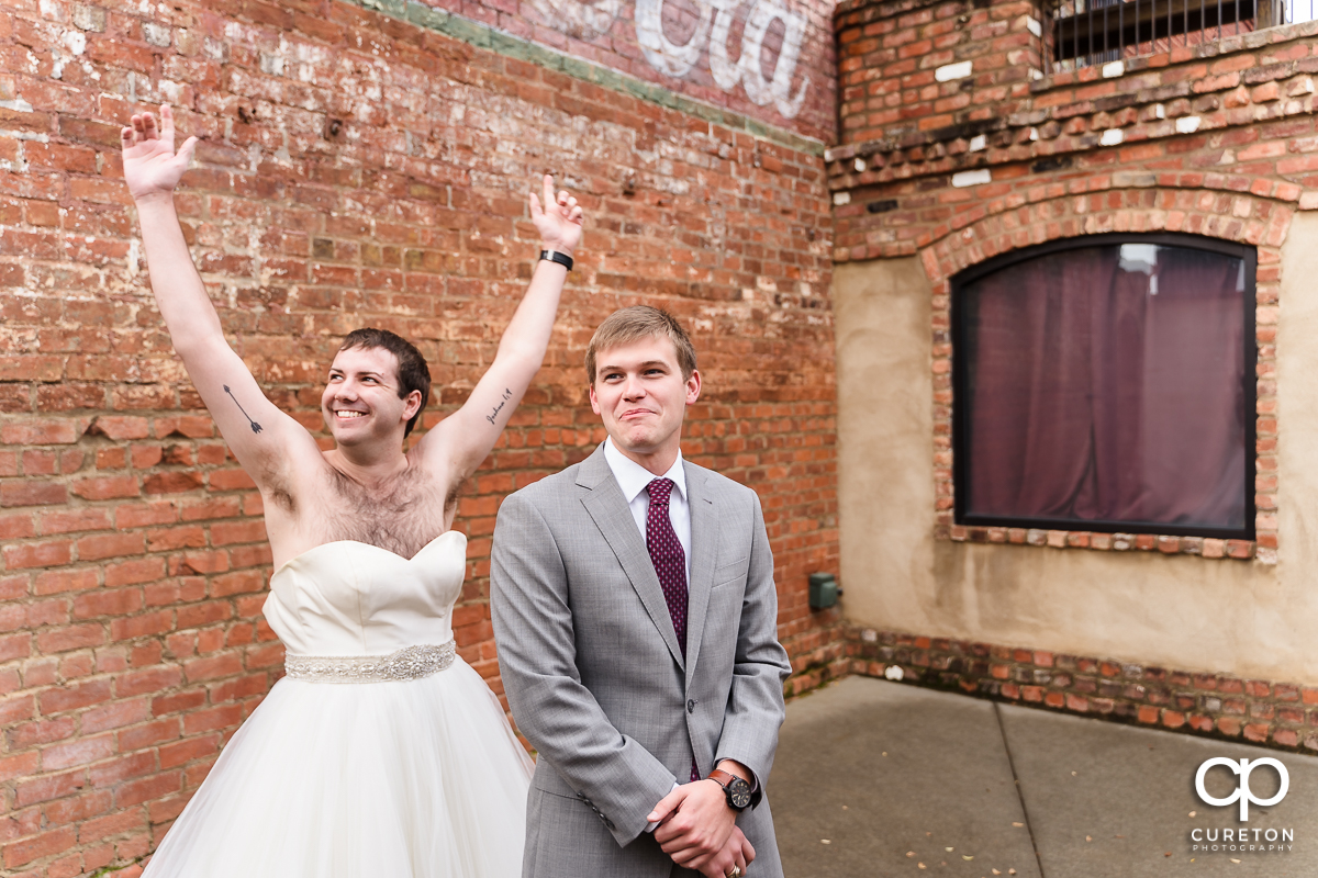 Groomsmen in a wedding dress showing up to the first look to trick the groom at The Old Cigar Warehouse as the bride looks on.