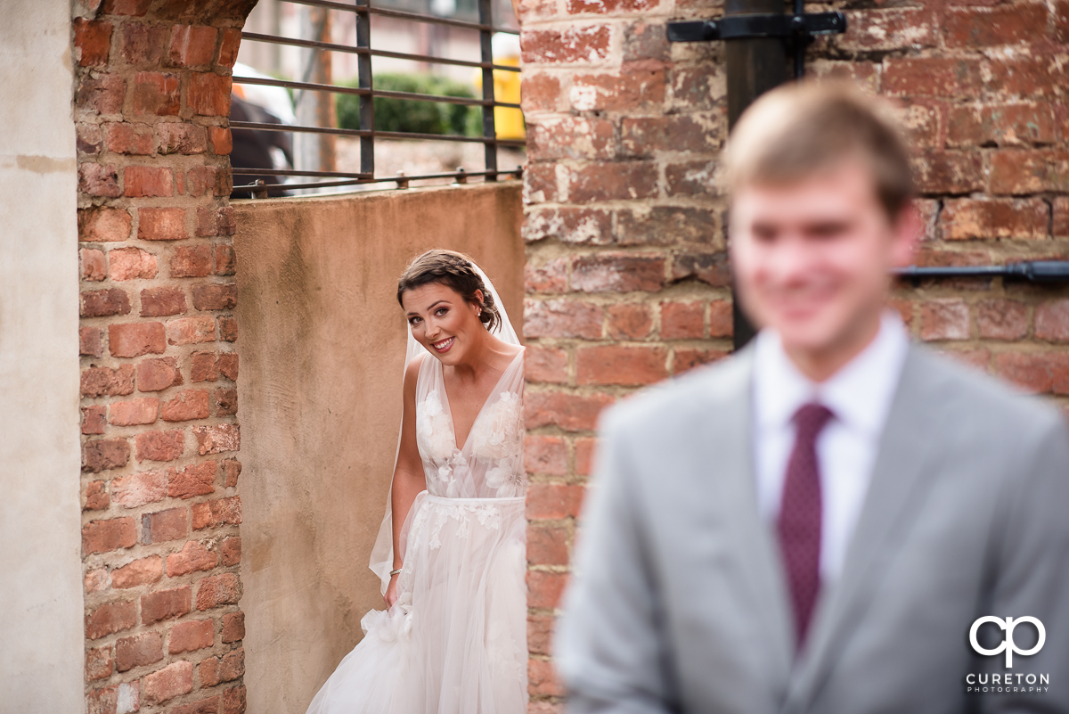 Bride sneaking up on the groom for a first look before the Old Cigar Warehouse wedding.