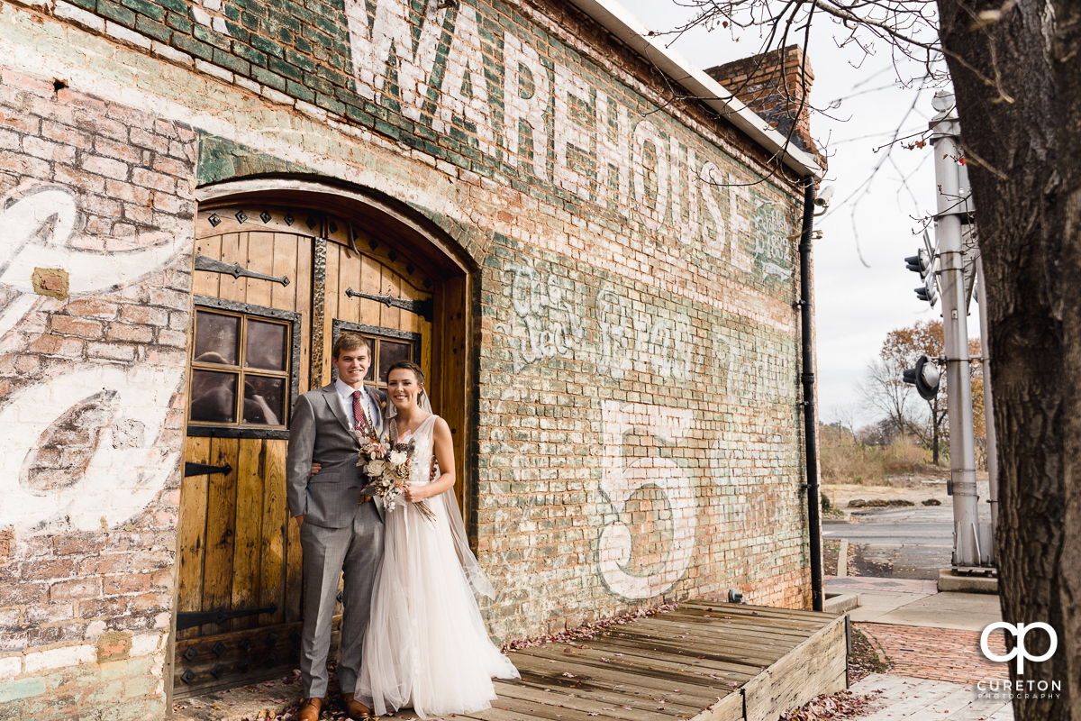 Bride and groom standing on the back deck of The Old Cigar Warehouse.