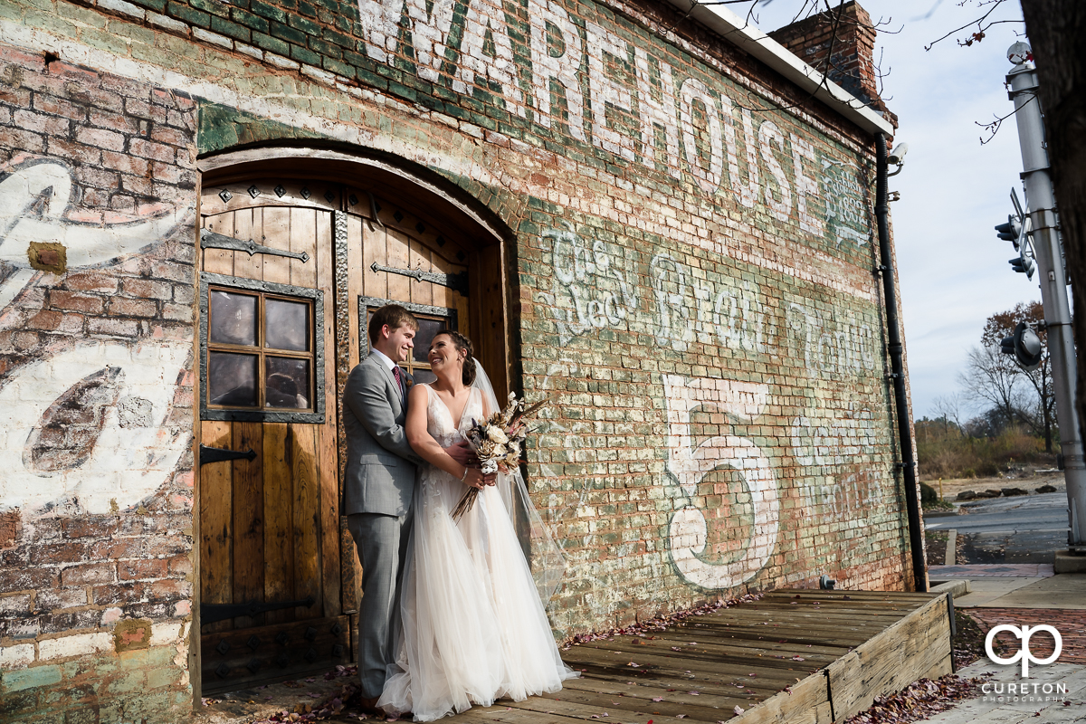 Bride and groom hugging on the back deck of The Old Cigar Warehouse before their wedding.