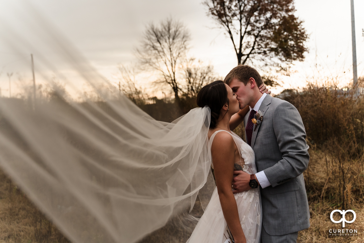 Bride and groom kissing as her veil blows into the breeze.