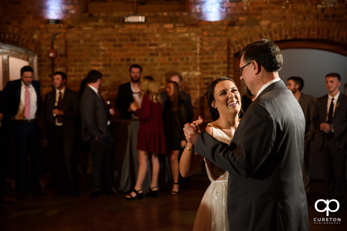 Bride smiling at her dad as the dance at the reception.