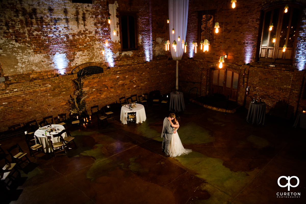 Bride and groom sharing a private dance at the wedding reception in the main hall of the Old Cigar Warehouse.