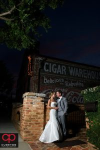 Bride and Groom standing underneath the sign at The Old Cigar Warehouse.