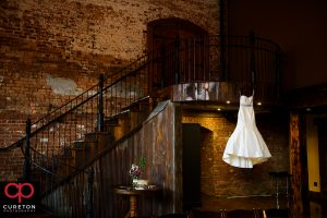 The bride's dress hanging on the staircase.