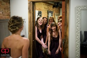 The bridesmaids seeing the bride for the first time.