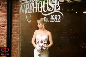 A bride looking through the window at the Old Cigar Warehouse.