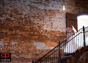 Bride and her mom walking down the stairs at Old Cigar Warehouse.