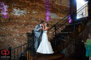 Bride and groom kissing on the steps.