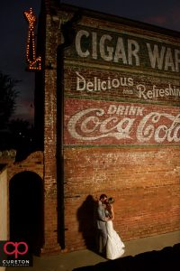 The bride and groom at night in front of The Old Cigar Warehouse.