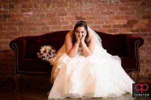 Bride sitting on a red couch during her Old Cigar Warehouse bridal session..
