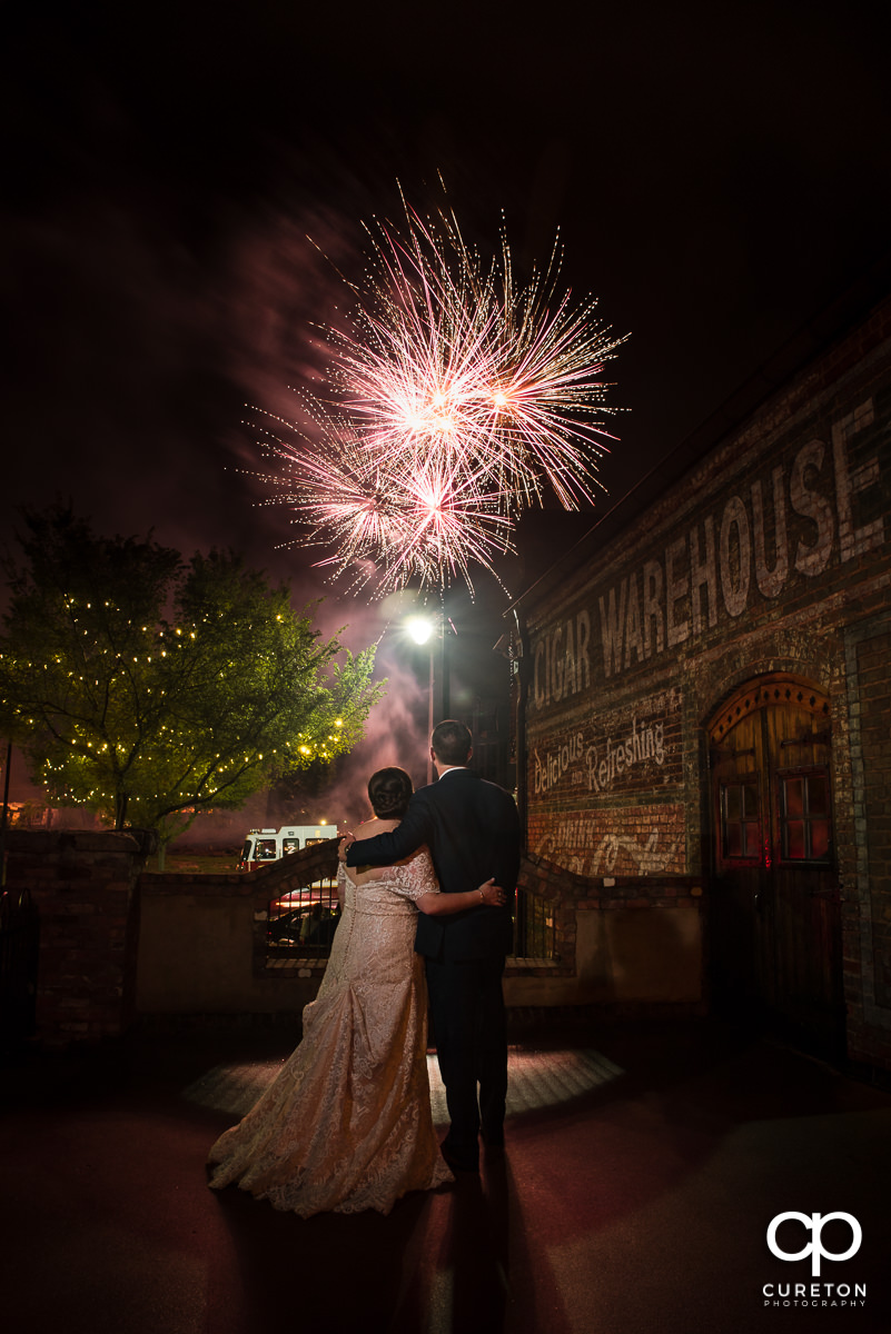Epic shot of a bride and groom looking at fireworks at their Old Cigar Warehouse Wedding in downtown Greenville,SC.