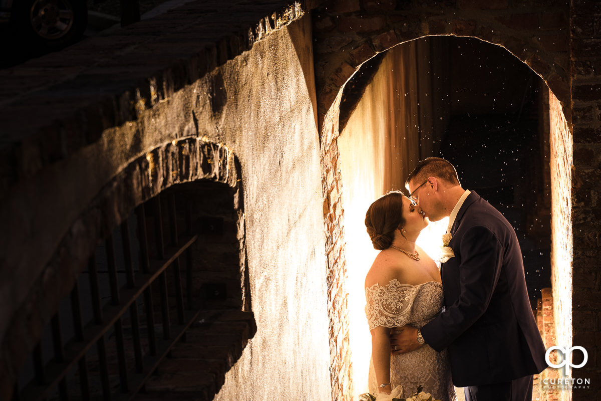 Bride and groom glowing in an archway kissing at twilight in the rain after their Old Cigar Warehouse Wedding in downtown Greenville,SC.