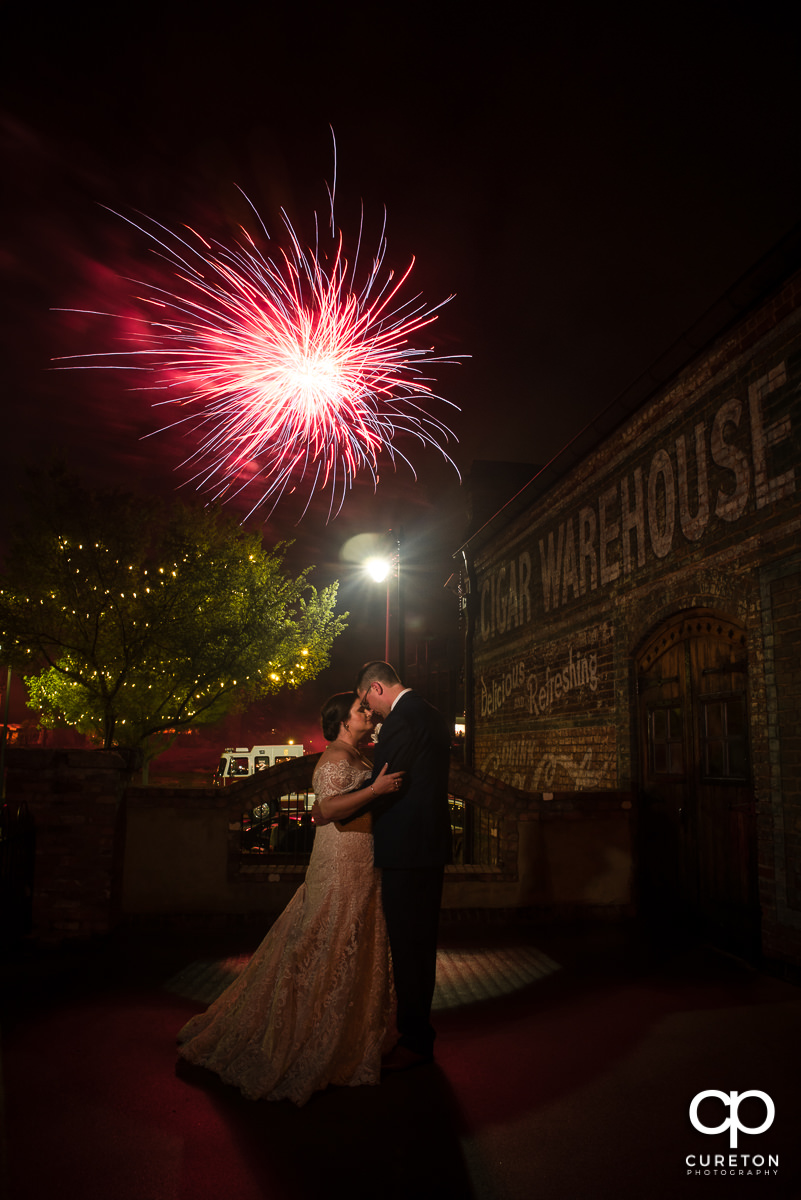 Bride and groom underneath some fireworks at their Old Cigar Warehouse Wedding in downtown Greenville,SC.