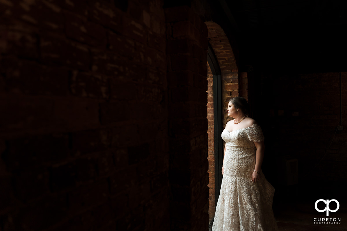 Bride looking out the window of the Old Cigar Warehouse.