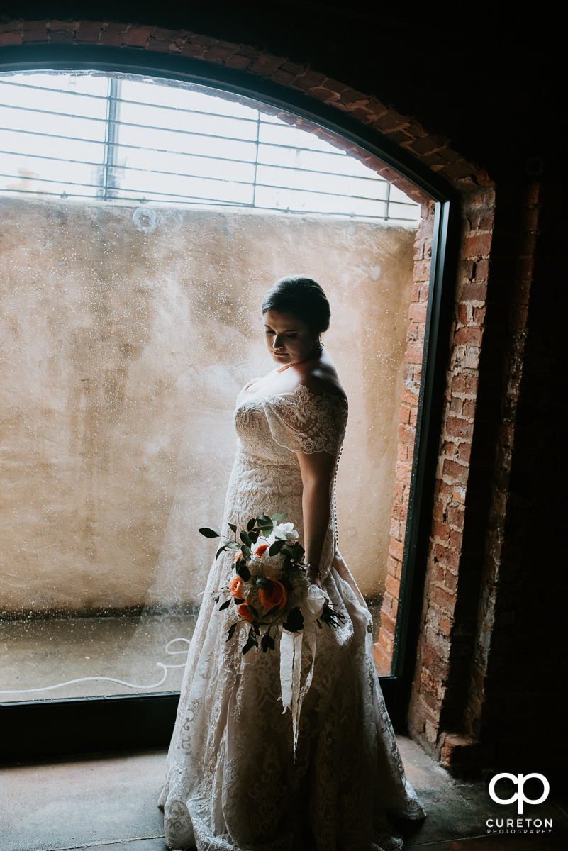 Bride looking at her bouquet in front ofd a window in the cellar at The Old Cigar Warehouse on her wedding day.