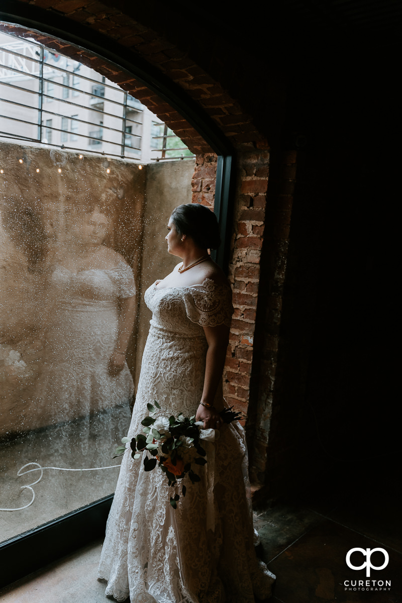 Bride looking out of the window in the cellar at Old Cigar Warehouse.