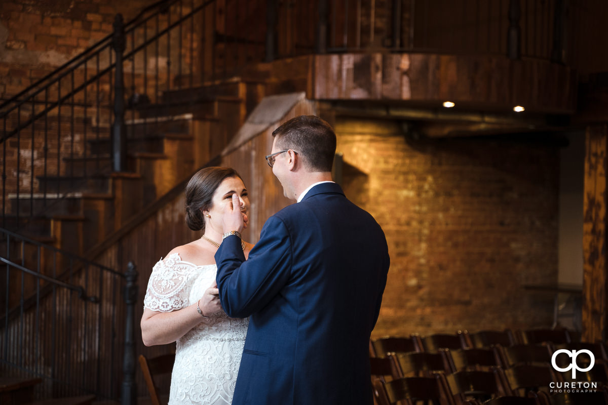 Groom wiping a tear away during a first look at The Old Cigar Warehouse.