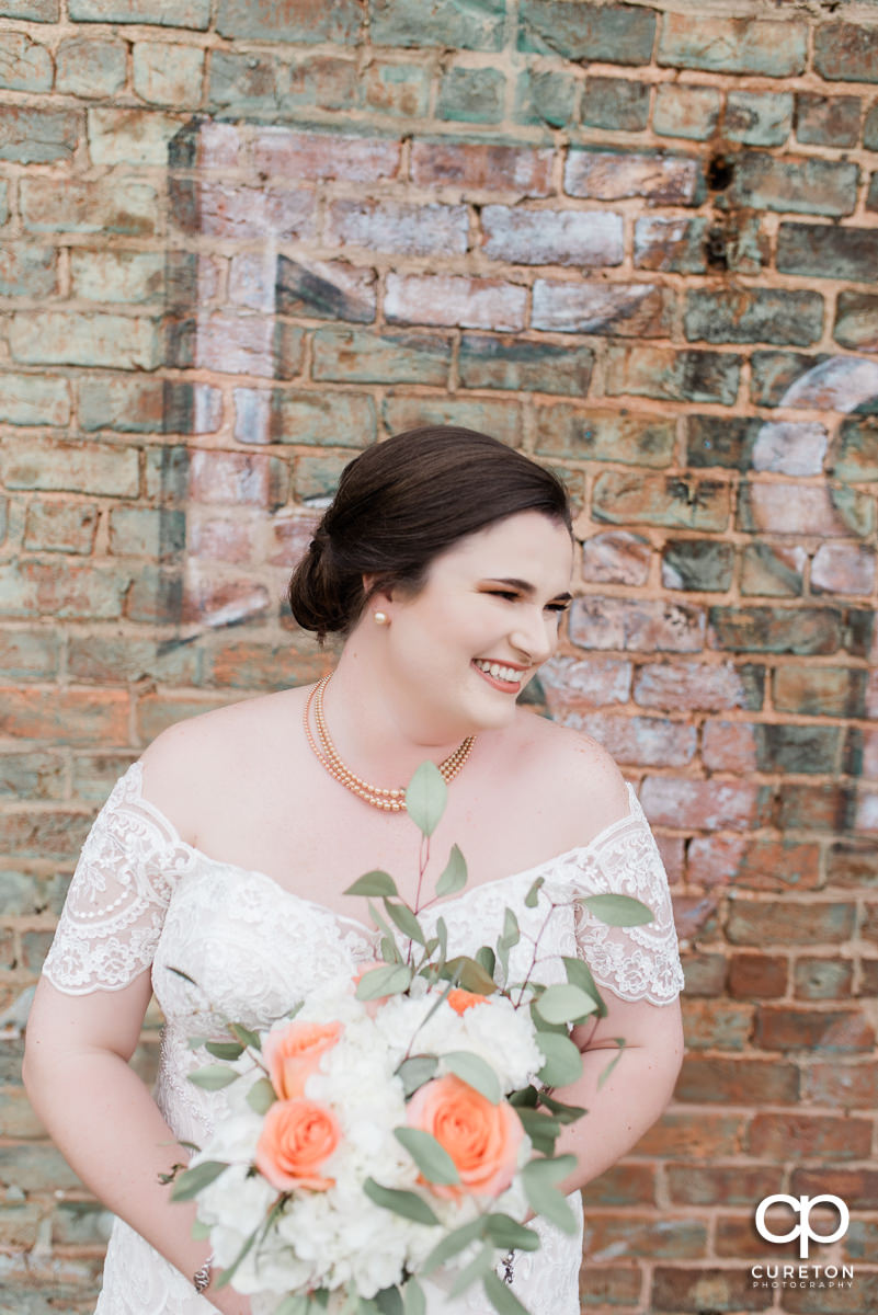 Bride smiling with her bouquet on the deck of The Old Cigar Warehouse.