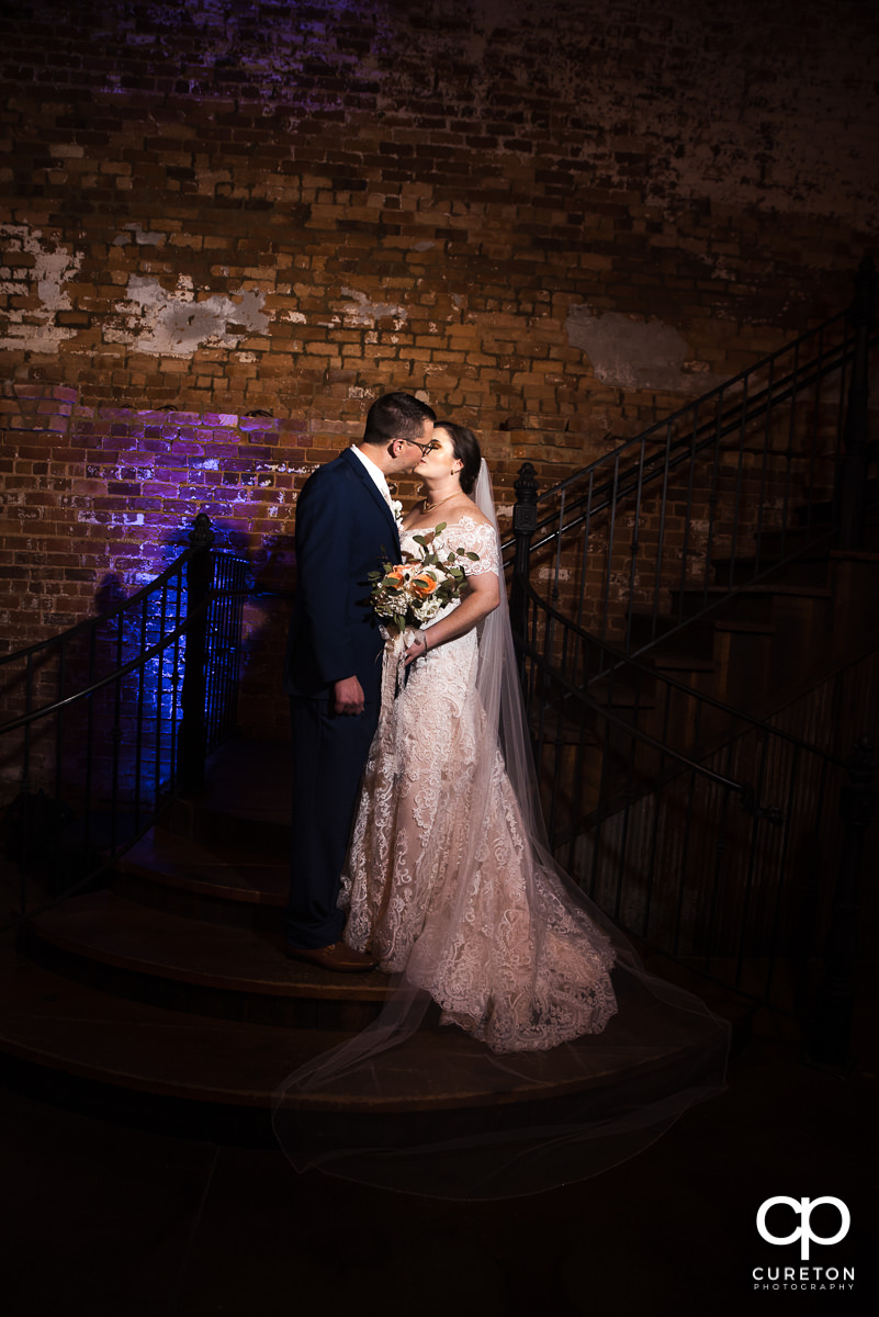 Bride and groom on the steps at Old Cigar Warehouse.
