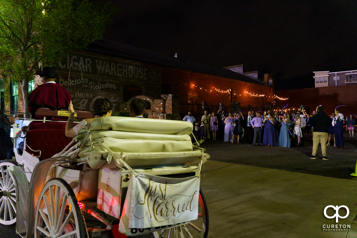 Bride and groom leaving The Old Cigar Warehouse wedding in a horse drawn carriage.
