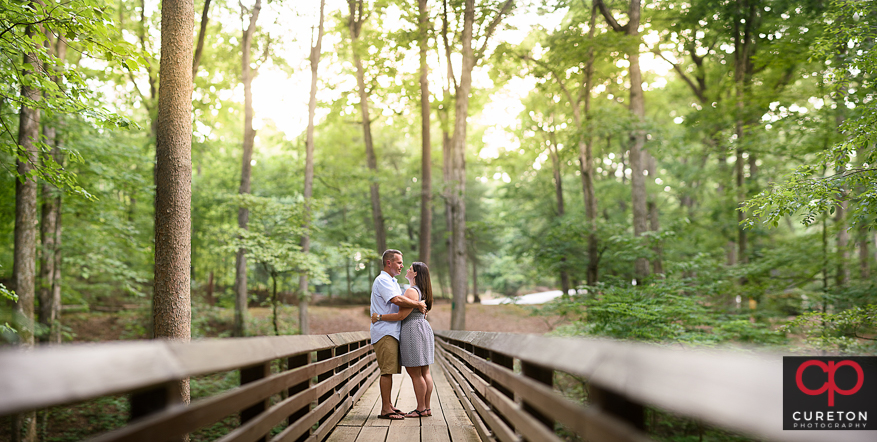 Engaged couple on a walking bridge during an engagement session at Paris Mountain State Park in Greenville,SC.