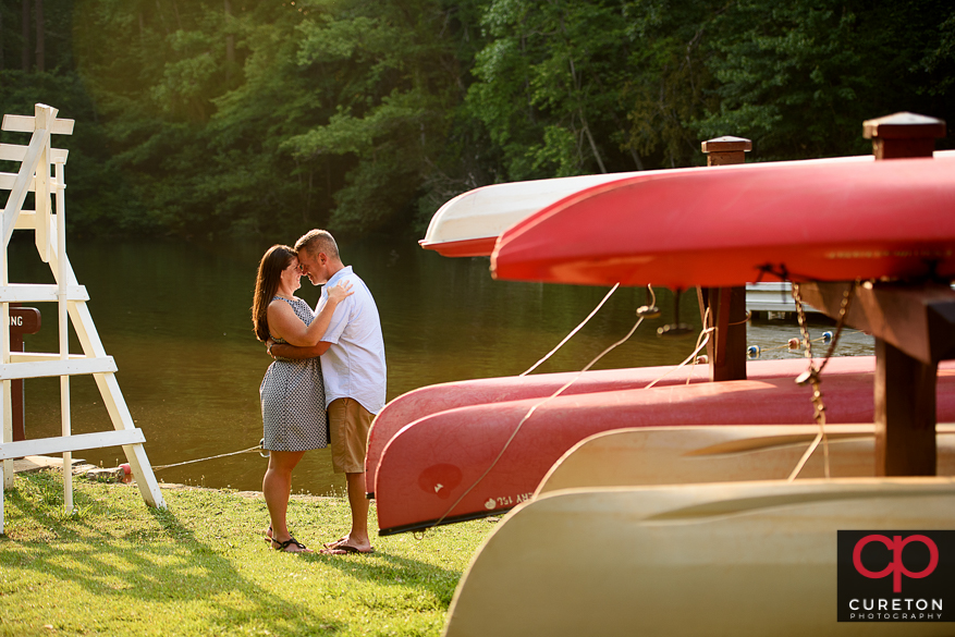Couple kissing beside some canoes at the lake during an engagement session at Paris Mountain State Park in Greenville,SC.