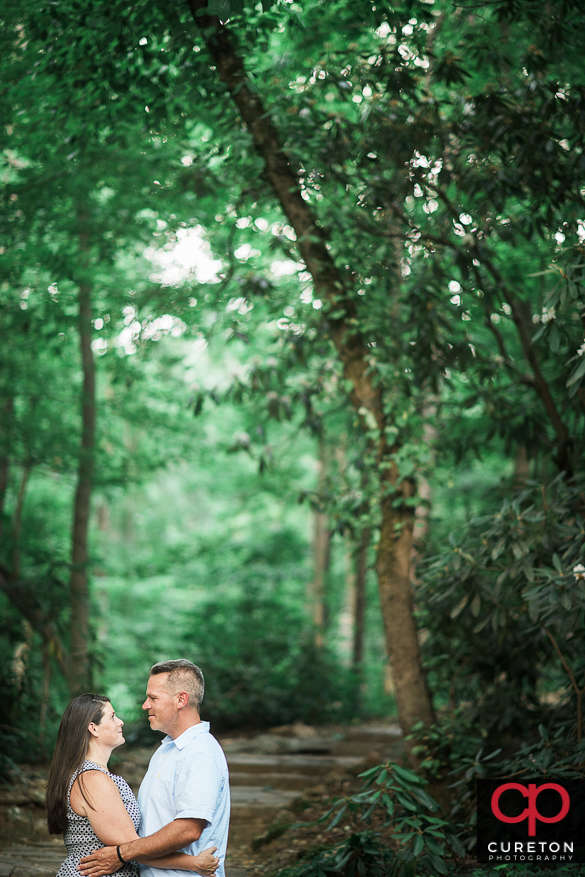 Couple cuddling in the woods during an engagement session at Paris Mountain State Park in Greenville,SC.