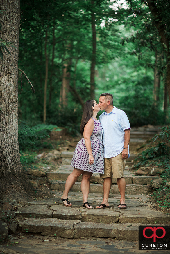 Couple stopping on some stairs for a kiss during an engagement session at Paris Mountain State Park in Greenville,SC..
