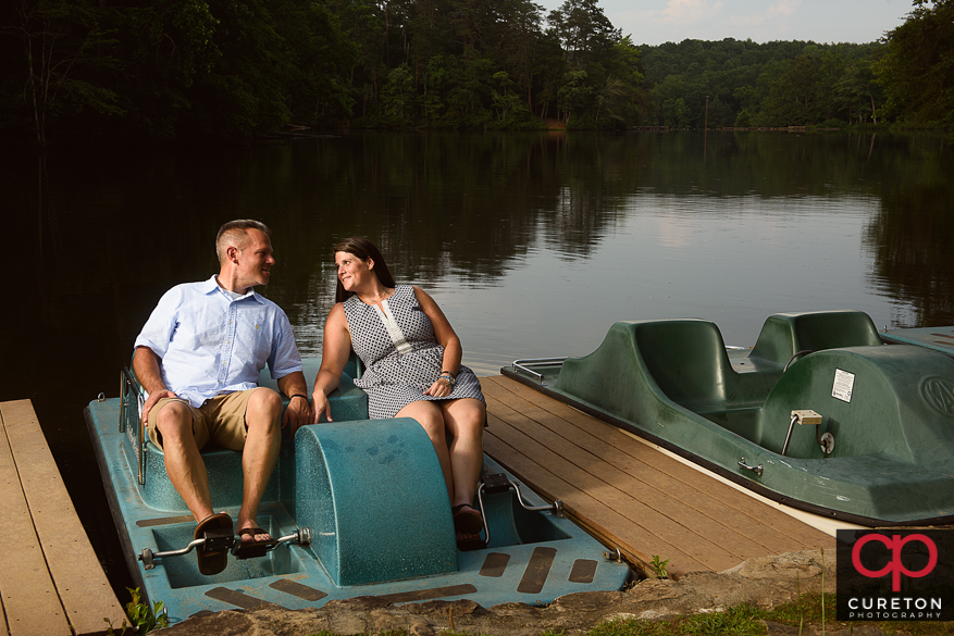 Engaged couple sitting on a paddel boat.