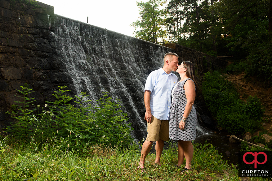 Engaged couple kissing near a waterfall.