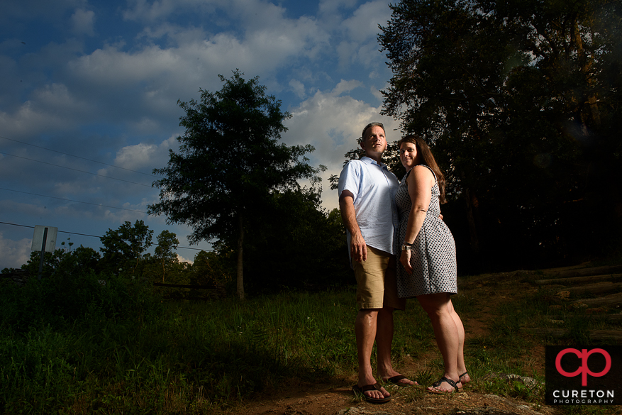 Engaged couple with epic sky behind them.