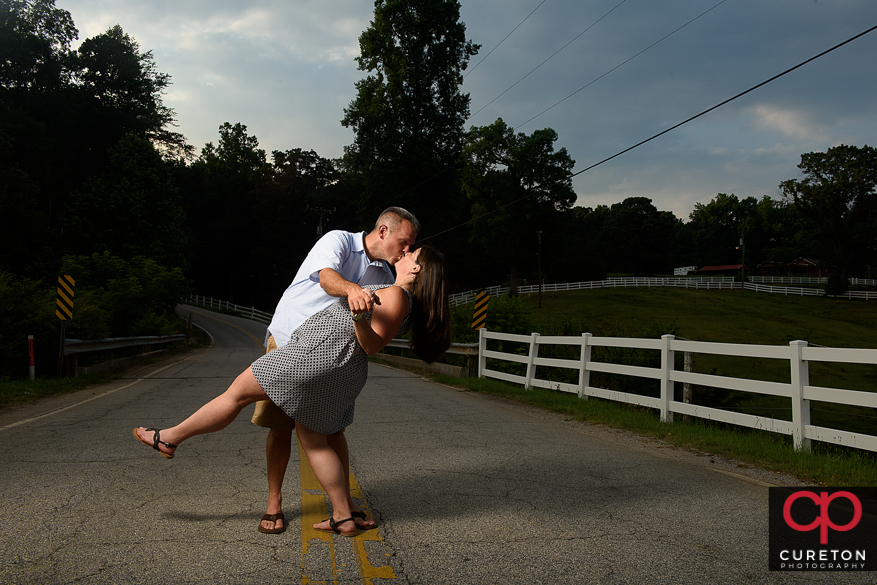 Engaged couple dipping in the road during an engagement session at Paris Mountain State Park in Greenville,SC.