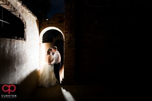 Bride and Groom standing in an archway during their Old Cigar Warehouse wedding reception.