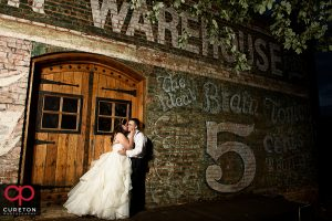 Bride and groom kissing by the Old Cigar Warehouse sign during their wedding reception.