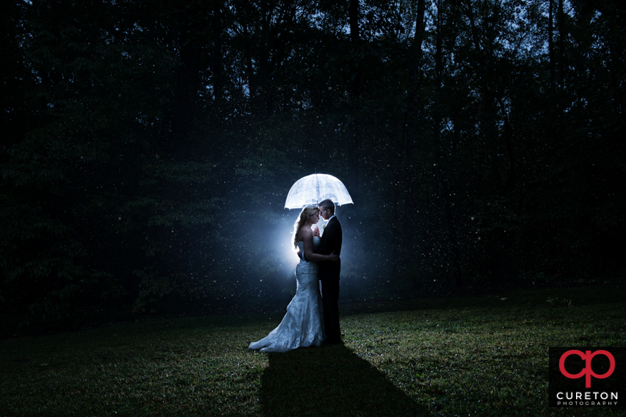 Bride and groom standing under an umbrella in the pouring rain.