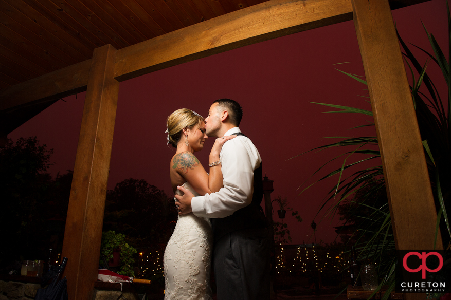 Married couple kissing under the red sky after a pouring rain.