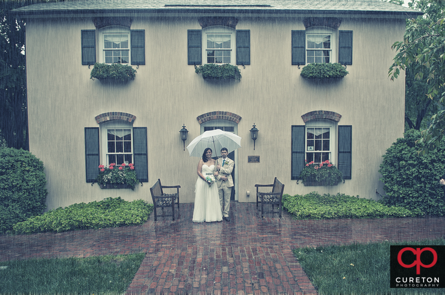Bride and groom standing in the rain.