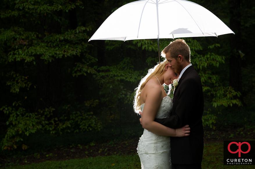 Couple after thier rain wedding under an umbrella.