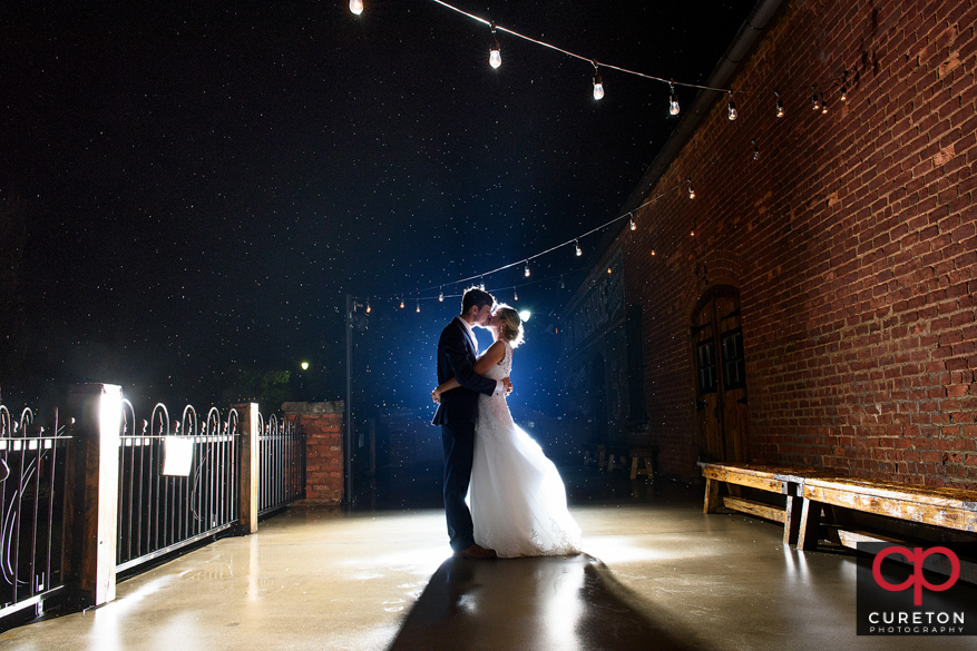 Couple in the rain on the deck of the Old Cigar Warehouse during a wedding reception.