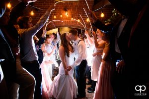 Bride and groom making an epic glow stick exit at The Old Cigar Warehouse wedding reception.