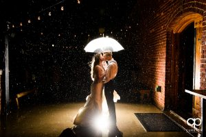 Bride and groom dancing in the rain at their Old Cigar Warehouse rainy day wedding reception.