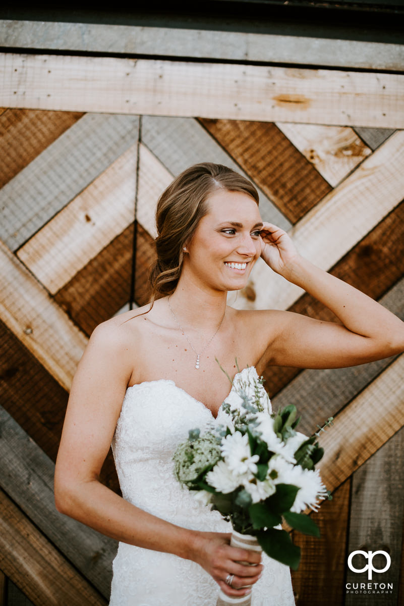 Bride laughing while fixing her hair during a bridal session in Greenville,SC.