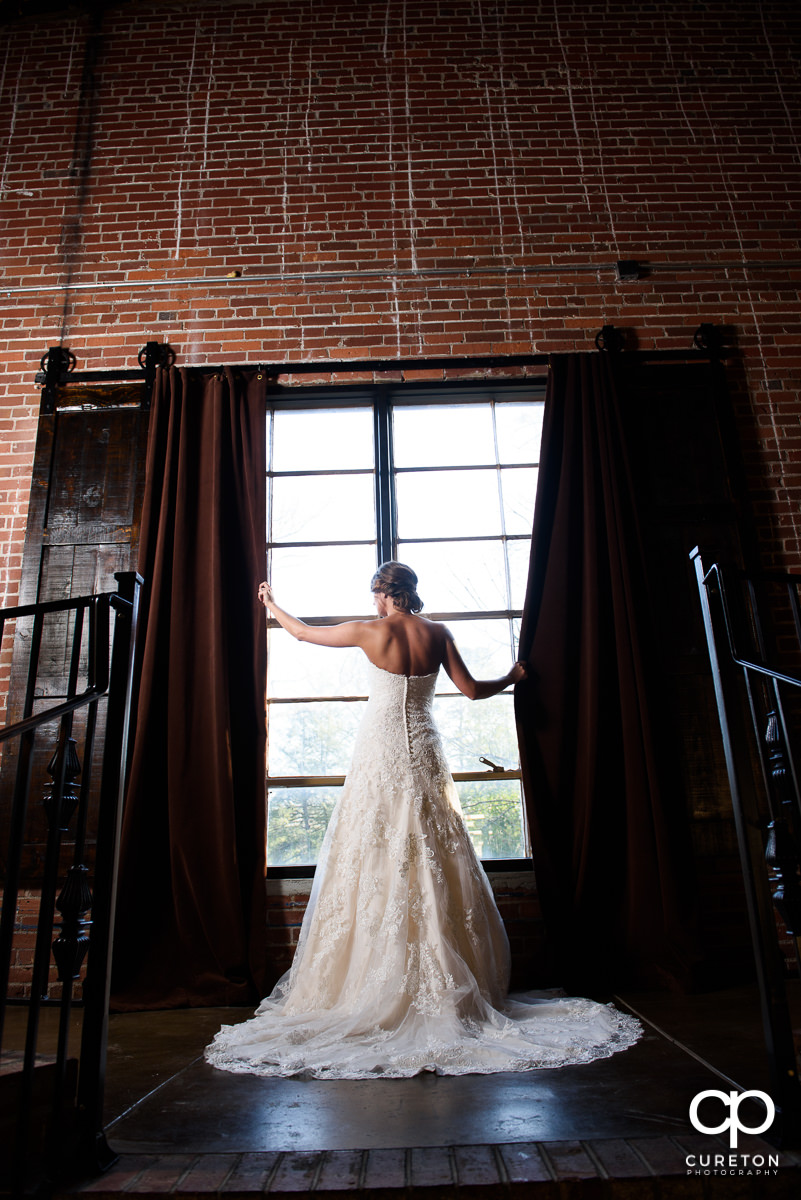 Bride standing in the window.