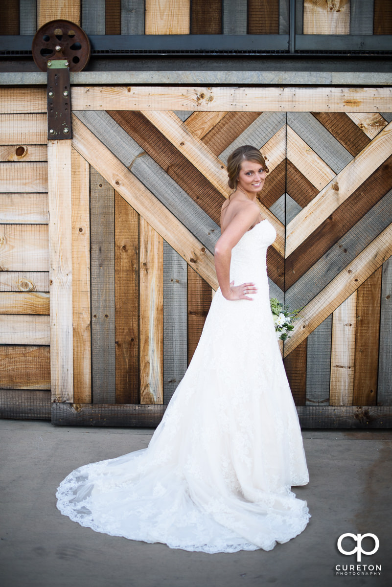 Bride standing in front of a wooden door.