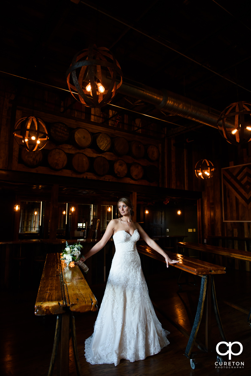 Bride in front of some whiskey barrels in the bar during a bridal session in Revel.