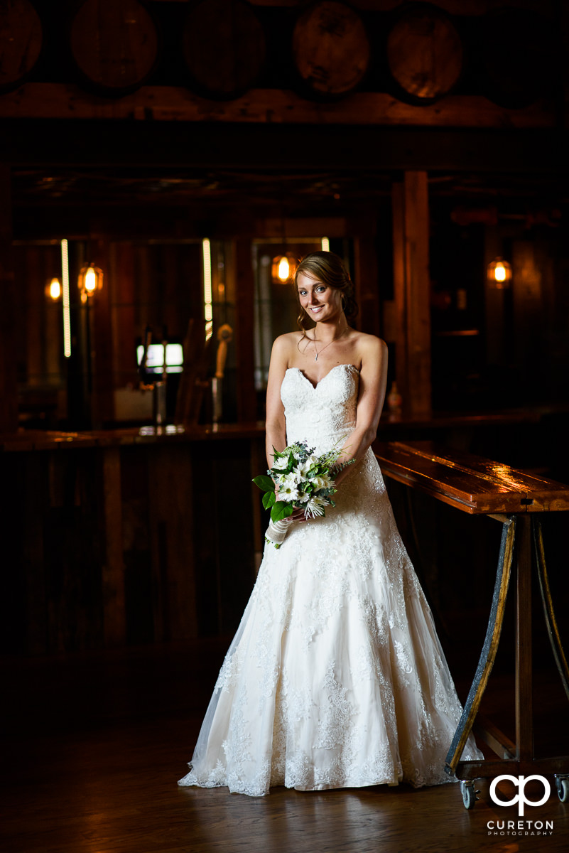 Beautiful all bride standing in a rustic bar during a bridal session.